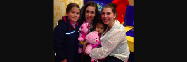 Two young women and two young girls with teddy bears, all smiling at the camera