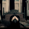 screenshot of video for Korn song Alone I Break, showing lead singer with head in hands sitting on bed alone