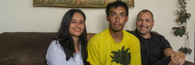 Matt Vinnola (center) sits with his mother, Janet van der Laak, and stepfather, Onne van der Laak, at the van der Laaks' Denver apartment on July 25, 2019