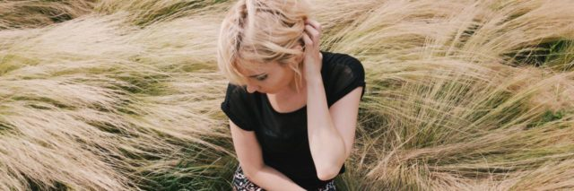 photo of blonde woman sitting in field of long grass looking away with hand in hair