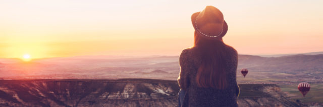 a girl with a hat sitting watching the sunrise above mountains