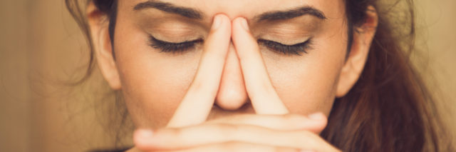 A woman sits with her eyes closed with her fingers rubbing her nose.