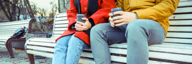 photo of 2 people sitting on a bench in fall clothes with coffee in their hands