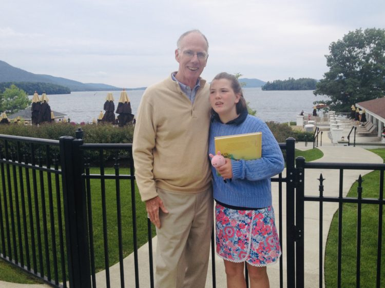 A teenage girl is standing with her late grandfather