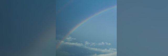 original photo by author of a blue sky with a rainbow