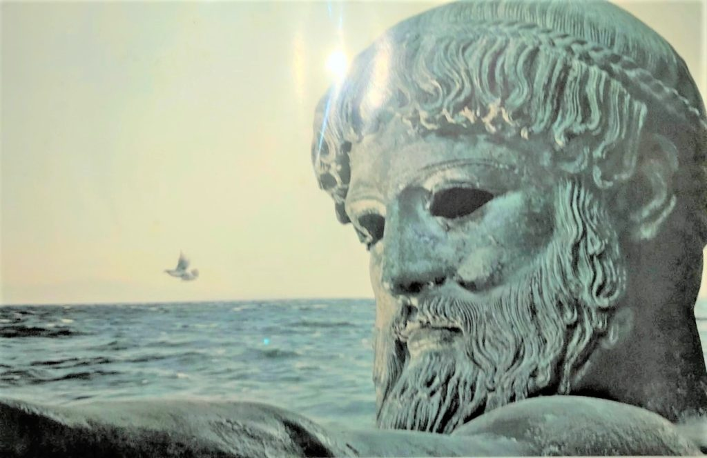 photo of a photograph showing a statue of poseidon beside the ocean, a light glare on his forehead