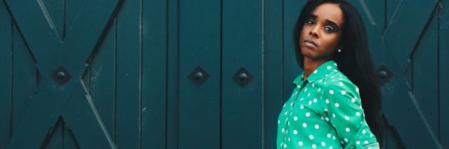 photo of woman standing in front of teal colored wooden doors with hands in skirt pocket