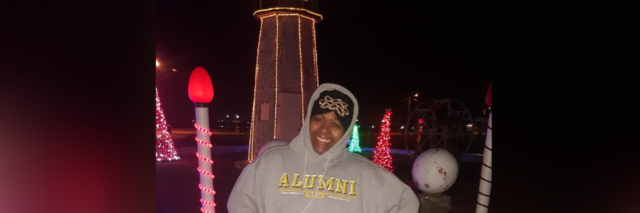 Jae posing outside with Christmas lights.
