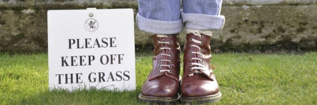 person standing next to a sign saying please keep off the grass
