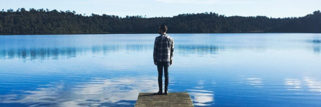 man in a flannel shirt and beanie standing on a long dock looking out into the blue water with clouds reflecting down