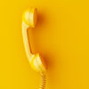 intage phone reciever on yellow background.