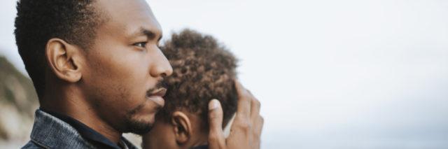 a black man cradling a little boy