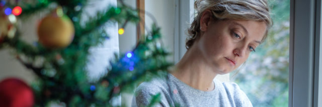 woman leaning against window sad, looking at christmas tree