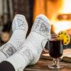 Woman wearing fuzzy socks relaxing by fireplace.