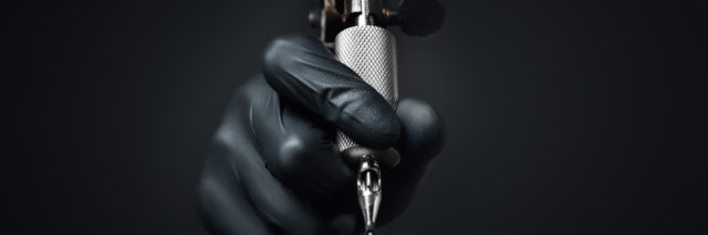 Gloved hand holding a tattoo needle