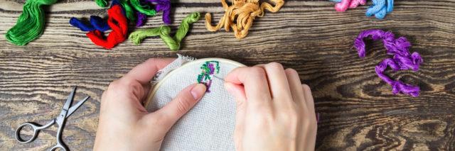 woman's hands cross-stitching