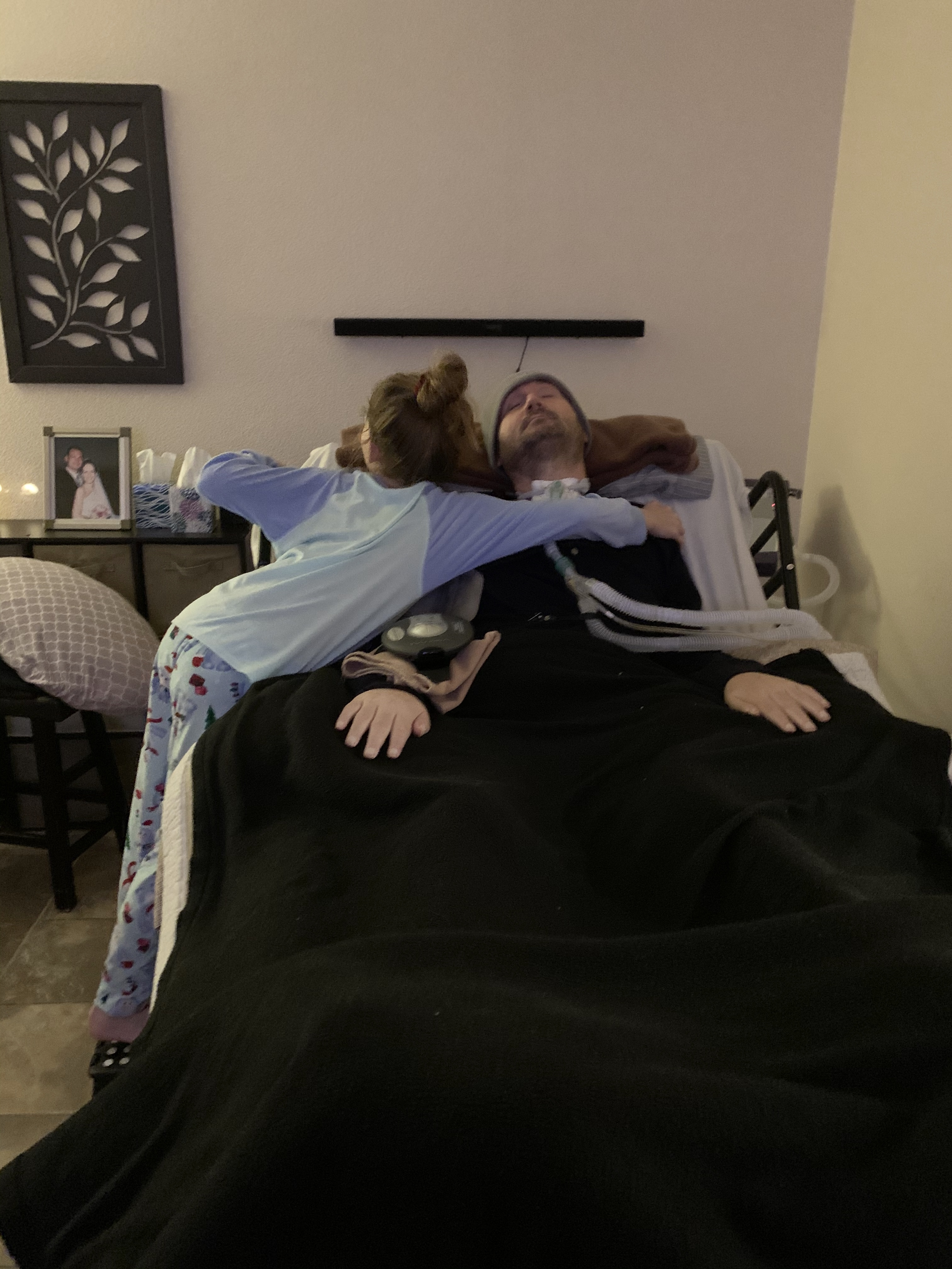 Jeff's daughter giving him a hug as he lies in bed.