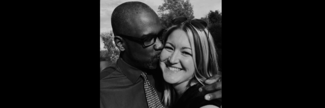 A woman stands smiling with a man next to her kissing her on the cheek