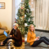 A split screen of two women, sitting down on their laptops in front of a Christmas tree