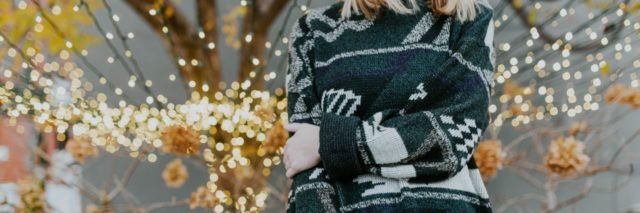 neck down picture of a woman in a green Christmas sweater standing in front of a lighted tree