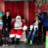 Tylia Flores sits in her wheelchair next to Santa Claus, with other relatives nearby.