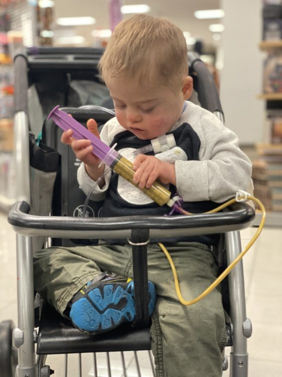 a little boy in a stroller getting a tube feeding at a store