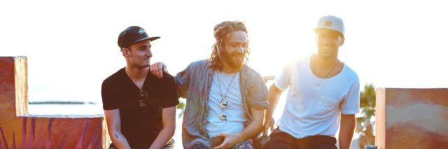 3 men sitting on a ledge smiling and hanging out