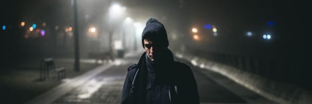 man in a beanie and blue jacket walking with his head down on a dark, cold sreet