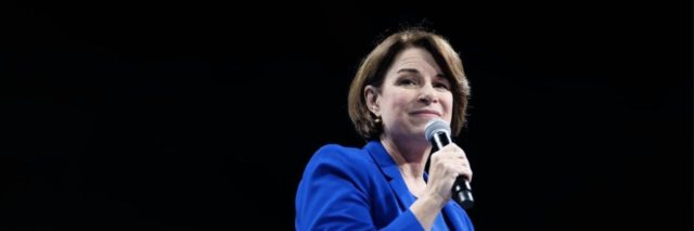 Amy Klobuchar wearing a blue suit, holding a microphone.