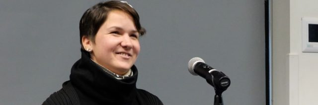 Karina, a woman with short brown hair sits at a podium and speaks to an audience. She smiles.