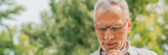 Man sitting outside on park bench thoughtfully looking at a tablet