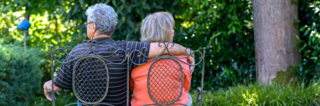 an older couple sitting on a bench in a green garden