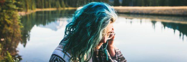 woman sitting near a peaceful lake