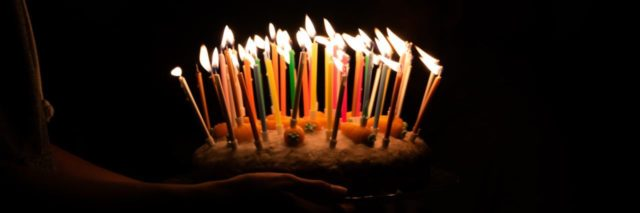 person carrying a birthday cake with many candles lit in the dark