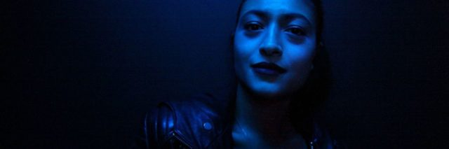 photo of woman in dark blue light posing for camera