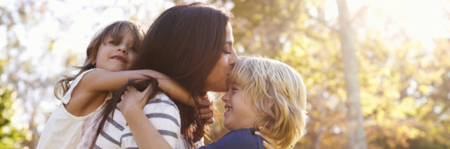 mother holding son kissing his forehead with her daughter on her back holding onto her