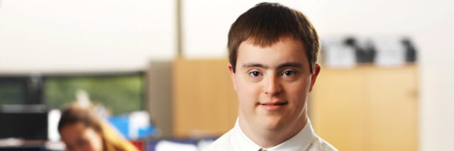 Man with Down syndrome working in an office.
