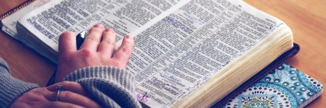 girl's hands on her bible reading