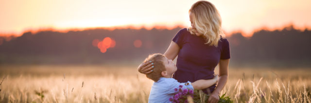 Boy hugging his mother in a summer meadow.