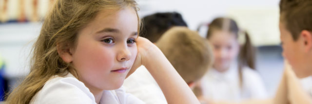 Close up shot of a little girl at school who looks distant and upset.