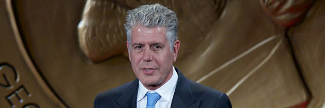 Anthony Bourdain accepts an award in a suit