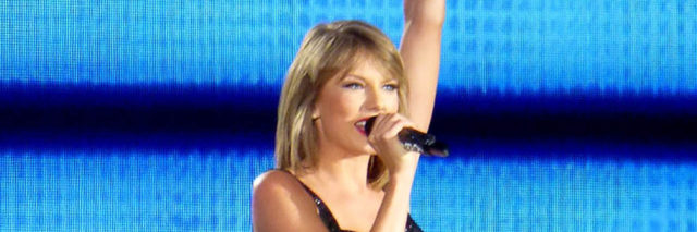 Taylor Swift performs onstage while wearing a black and blue outfit
