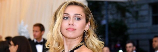 Miley Cyrus poses in a black dress while on the red carpet