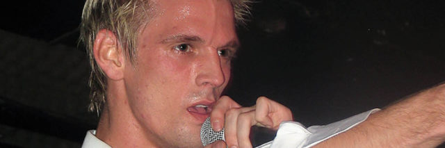 Aaron Carter singing onstage while at a concert