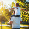 a young girl sitting on her dad's shoulders at apark