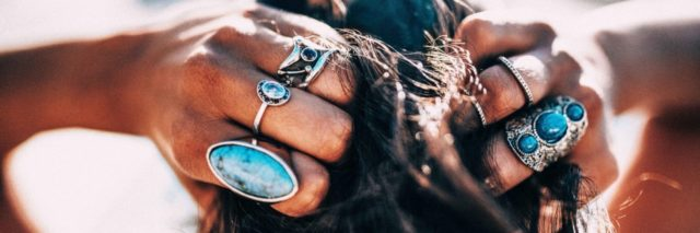 Woman with bohemian style jewelry rings on hands.