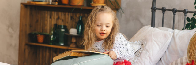 Girl with Down syndrome reading a book.