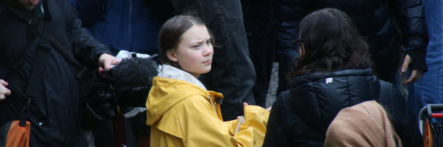 Greta Thunberg is surrounded by people at a protest
