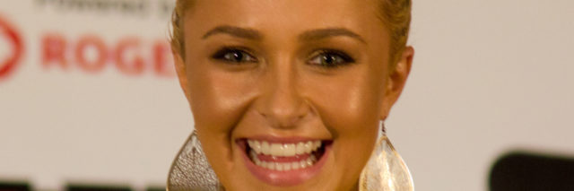 Hayden Panettiere smiles at an event in a yellow outfit