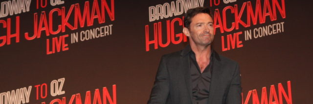 Hugh Jackman in a black suit looks ahead at a press conference